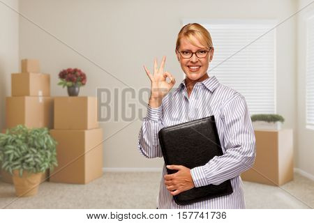 Female Real Estate Agent with Okay Sign and Binder in Empty Room with Packed Moving Boxes and Plants.