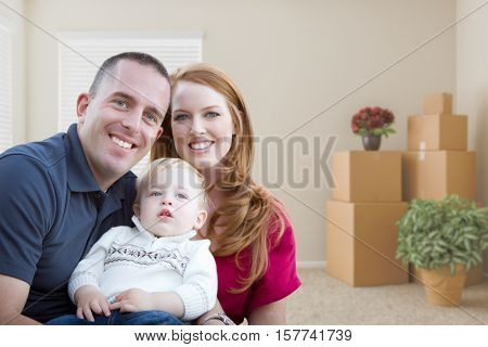 Happy Young Military Family in Empty Room with Packed Boxes and Plants.