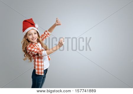 Here it is. Cheerful little girl celebrating New Year and smiling while standing isolated on grey background