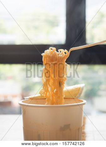 Noodles With A Plastic Fork On Wooden Table