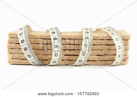 Pieces of crispbread with measuring tape isolated on white background. A symbol of diet