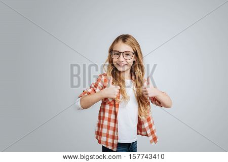 Full of gladness. Cheerful delighted smiling little girl thumbing up and smiling while expressing joy on grey background