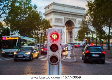 traffic lights in Paris with city traffic and Arc de Triomphe in background