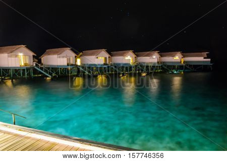 Abstract blur Milky Way over water villa cottages on Maldives