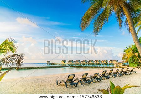 Beach chairs in Maldives island with water villas at the sunrise time
