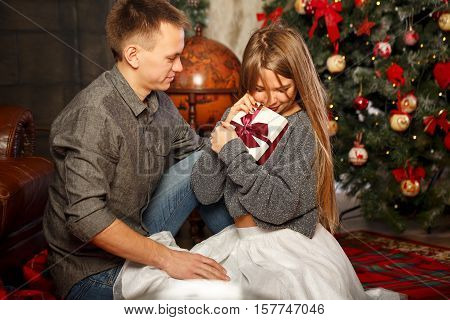 Loving couple and Christmas. Man gives a girl a Christmas gift. They sit on the floor near the fireplace. She is happy the present. In the background a beautiful Christmas tree.