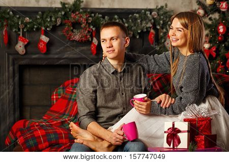 Loving couple and Christmas. Boyfriend and the girl sit on a couch and drinking a hot Christmas drink mulled wine. Girl barefoot. In the background a beautiful Christmas tree.
