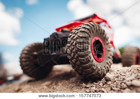 Red crawler wheels outside close-up. Rc car standing on rock, blue sky with clouds on background poster