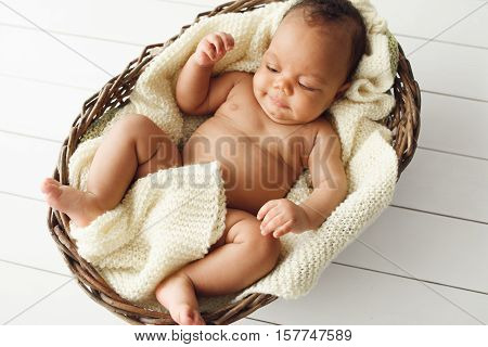 Newborn african baby in wicker basket, flat lay. Top view on cradle with adorable naked child, covered with white woolen blanket, white wooden background