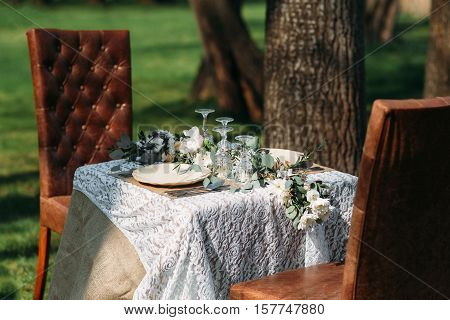 Dinner served for two outdoor, luxury lifestyle. Small table with two plates and silverware sets, decorated with green flowers, under tree with two cozy chairs