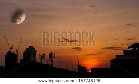 Scene of Super Moon with silhouette sunset over roof top view in town