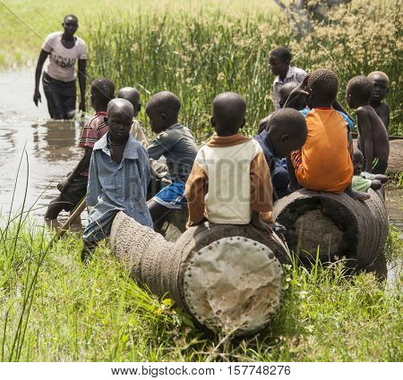 BOR, SOUTH SUDAN-NOVEMBER 2, 2013: Unidentified children play in dugout canoes south of Bor, South Sudan
