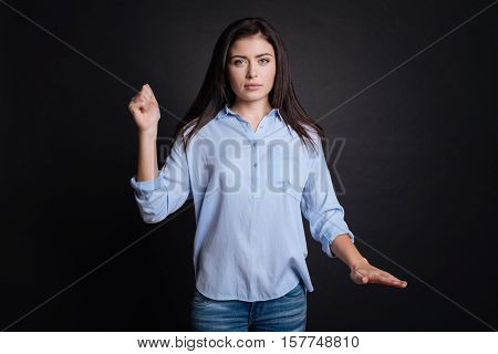 Emotional wave. Pleasant distressed woman using gestures and looing at you while standing gisolated on black background