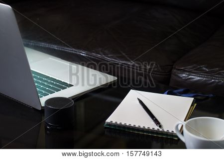 Laptop notebook and coffee cup on mirror table with black sofa blackground in living room