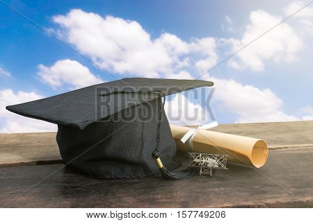 Graduation Cap, Hat With Degree Paper On Wood Table, Sky Background Empty Ready For Your Product Dis