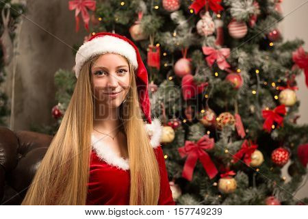 blonde woman dressed as Santa at the Christmas tree sitting on the couch