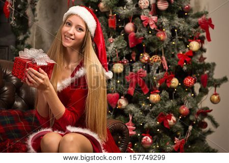 blond woman dressed as Santa at the Christmas tree sitting on the couch with a gift box in their hands