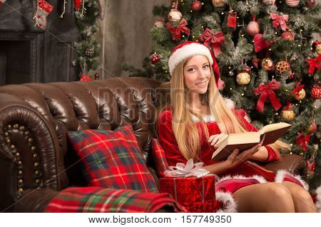 blonde woman dressed as Santa at the Christmas tree sitting on the couch with a book in their hands