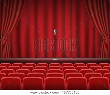 Rows of red cinema or theater seats in front of show stage with retro microphone