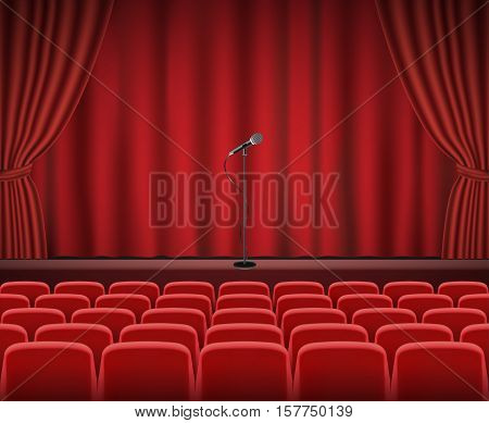 Rows of red cinema or theater seats in front of show stage with microphone