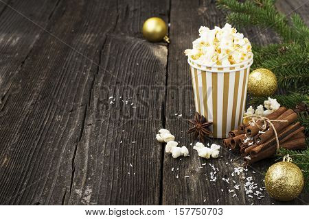Salty fresh crusty homemade popcorn in silver paper cup in the fashion light background of white brick wall in a New Year's interior with silver Christmas balls. selective focus
