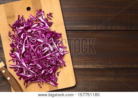 Raw red cabbage chopped on wooden board photographed overhead on dark wood with natural light