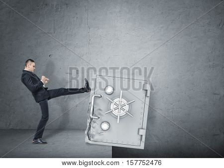 A businessman kicking a deformed safety box to throw it down in the pit. Business development and the way to success. Issues in business management and economics. Resolving the problems.