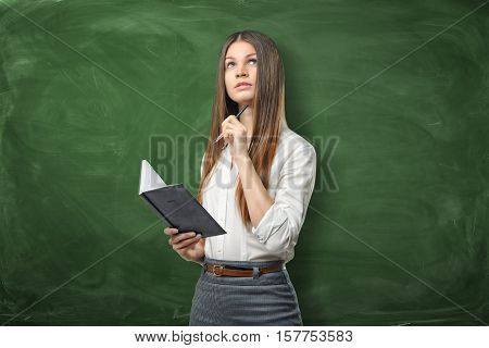 A young businesswoman holding her open day planner and a pen and going to write something on the green chalkboard background. Daily planning. Time-management. Secretary work.