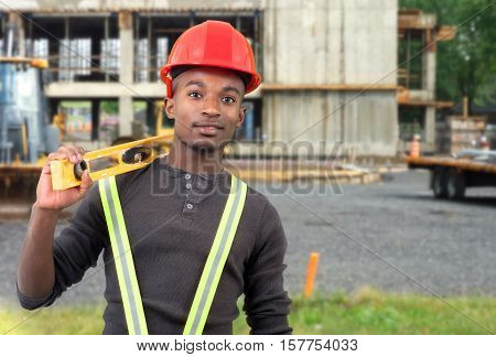 man on construction site working with level hardhat and pensil on ear