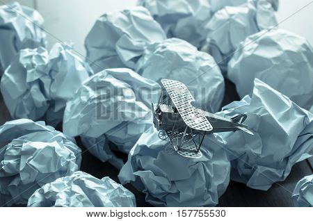 Plane Model With Crumpled Paper On Wood Background. Business Frustrations, Job Stress And Failed Exa