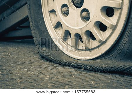 Damaged flat tire of an old car on the road with selective focus and vintage filter effect
