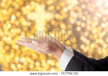 businessman pray with cross light on hand.