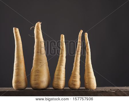 Five raw parsnip in a row on a rustic wooden table