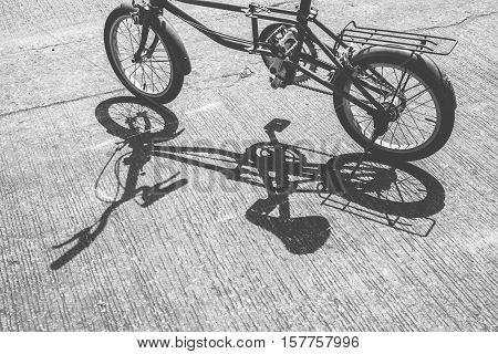 Shadow of folding bicycle in the sun with vintage effect