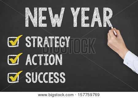 Human Hand Writing New Year Strategy on Chalkboard