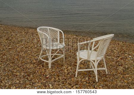 Two white empty chairs on the pebble beach