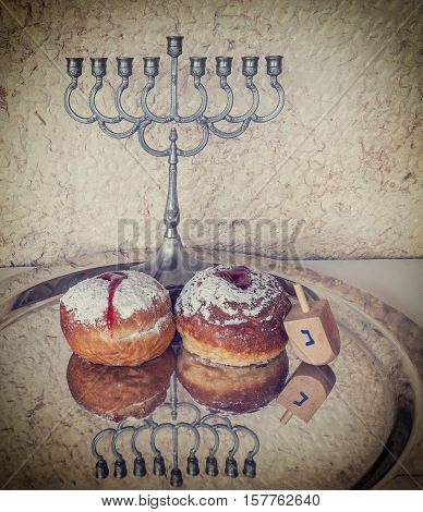 Festive sweet donuts, menorah and dreidel are traditional symbols of Hanukkah holiday. Selective focus. Image toned for inspiration of retro style.