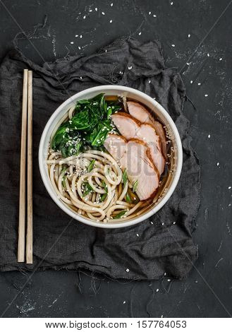 Spicy pork and noodle soup. On a dark background top view