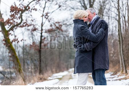 Senior woman and man embracing each other in winter