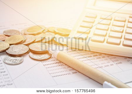 Business, finance, savings or mortgage background concept ; Coins, pen, calculator and savings account passbook on white background