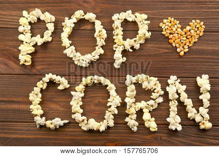 Words pop corn made of maize grains on wooden background