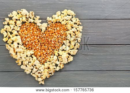Heart made of popcorn and maize grains on wooden background, top view