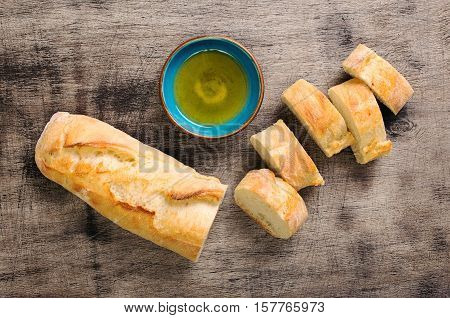 Fresh Italian baguette cut in slices on wooden table with oil top view