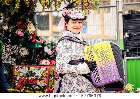 PARIS - MARCH 15 2015: A beautiful woman in vintage dress playing a traditional musical instrument, Accordion,  to show the tourists who came to visit Sacré-C