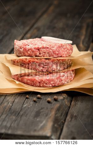 Raw ground beef meat cutlets on wooden table close up
