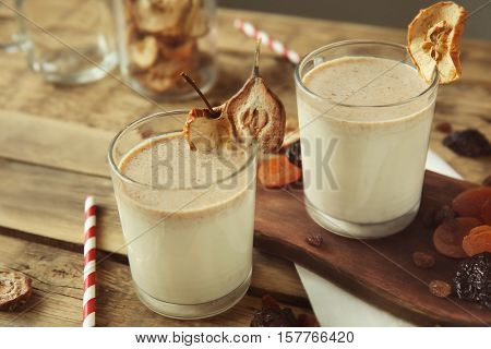 Milk shakes with dried fruits on wooden table