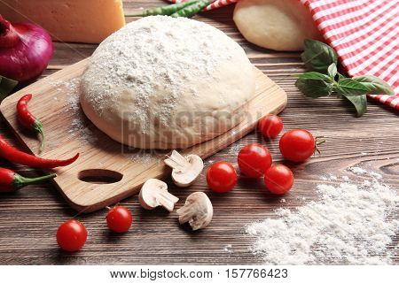 Raw pizza dough with ingredients on wooden table