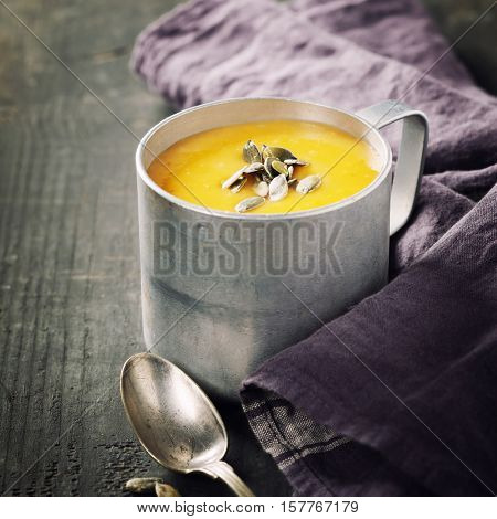 Pumpkin soup in a metal pot on a wooden surface