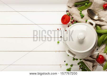 White cooking pot and ingredients for soup or stew on white rustic background, top view