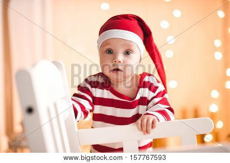 Surprised baby girl under 1 year old wearing santa claus suit posing over Christmas lights. Looking at camera. Holiday season.